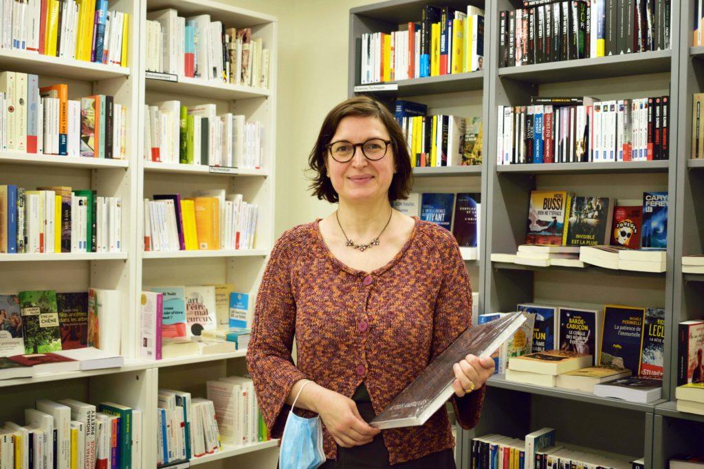 Librairie-Cheval-Vapeur-librairie-Vanves-Mme-Guler-Le-Pape-devant-son-rayon-de-sciences-sociales-au-sous-sol