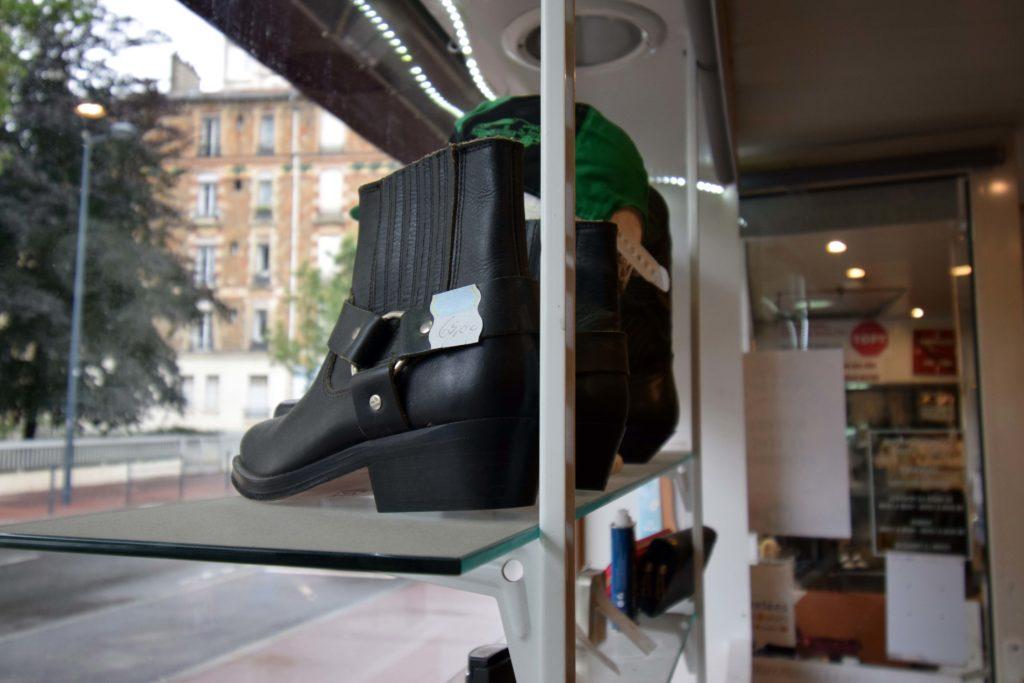 Cordonnerie-Chic-et-Choc-Cordonnerie-Vanves-detail-sur-des-bottines-en-cuir-de-la-vitrine-avec-vue-sur-la-porte-dentree